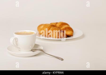 Petit déjeuner - café avec les croissants sur un fond blanc. Focus sélectif. Banque D'Images