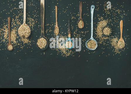 Télévision-laïcs de divers vieux millésime cuillères cuisine pleine de grains de sarrasin crus vert sur fond noir Banque D'Images