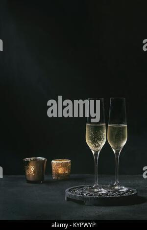 Deux verres de champagne servi blanc sur noir décoratif en bois avec des bougies conseil sur dark texture background. Banque D'Images