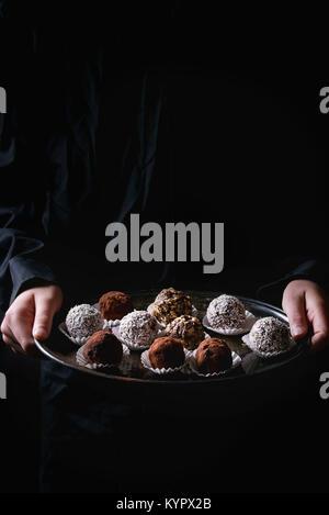 Variété de truffes au chocolat noir faites maison avec de la poudre de cacao, noix de coco, noix sur vintage plateau dans les mains d'enfant en chemise noire. Fond sombre.