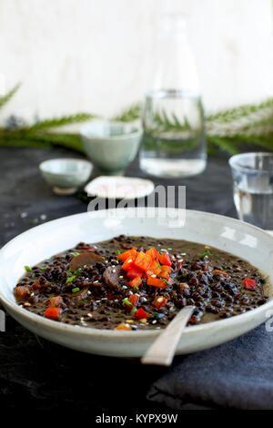 Lentilles Soupe Coco Sésame noir servi avec de l'eau pétillante. Photographié sur un fond gris foncé/noir. Banque D'Images