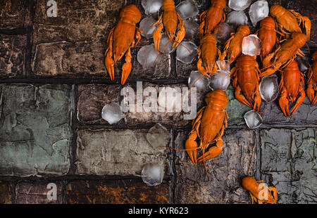 Vue de dessus de délicieux homards avec des cubes de glace sur la surface du mur de brique Banque D'Images
