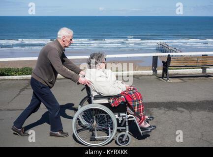 Vieil homme edlerly poussant woman in wheelchair sur front de mer. UK Banque D'Images