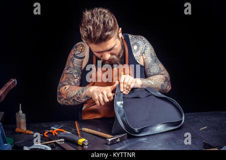 Currier en cuir cuir découpe les contours de sa nouvelle production à sa zone de travail Banque D'Images