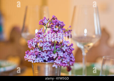 Fleurs lilas que spring bouquet dans un gobelet de métal sur une table avec des verres à vin à l'arrière-plan. Des tons chauds dans un intérieur cosy.