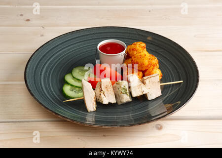 Morceaux de filet de poulet sur une brochette avec des boules de pommes de terre frites et légumes Banque D'Images