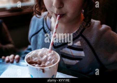 Portrait playful girl blowing bubbles dans du lait au chocolat à la maison Banque D'Images