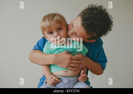 Portrait of cute baby boy avec le frère de l'embrasser contre le mur à la maison Banque D'Images