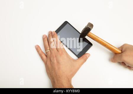 Frapper un homme de l'écran du smartphone avec un petit maillet, dans un concept de verre incassable dans une vue Banque D'Images