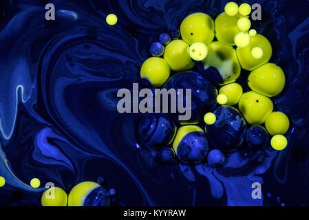 Gouttes d'huile jaune bleu suspendu dans la création d'une nappe de pétrole produits chimiques résumé entre la nature Banque D'Images