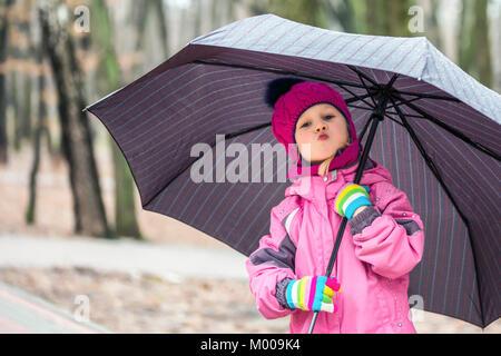 Adorable petit caucasian girl wearing pink hat tricoté veste chaude et marcher sous parapluie dans un parc de la Banque D'Images