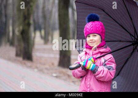 Portrait of little adorable caucasian girl wearing pink hat tricoté veste chaude et marcher sous parapluie dans Banque D'Images