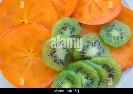Frais mûrs juteux kiwi tranches avec persimmon disposées sur une plaque, vue d'en haut