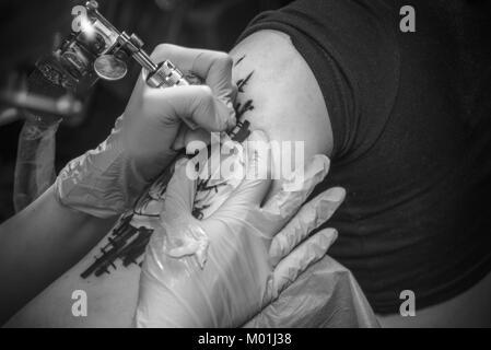 Maître tatouage montrant processus de faire un tatouage dans un atelier studio./Professionnel tattooer faire l'art Banque D'Images