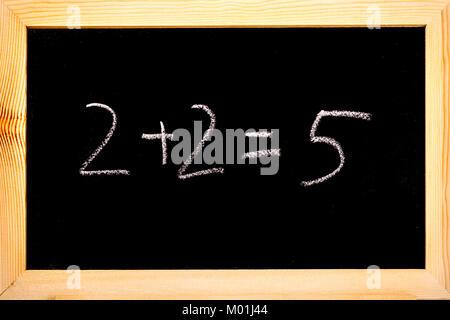 Tableau noir avec 2+2=5 sur l'écrit en blanc craie. Banque D'Images