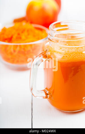 Le jus de carotte par Apple sur une table en bois blanc. Boisson saine. Régime alimentaire. Bébé en santé l'alimentation. Banque D'Images