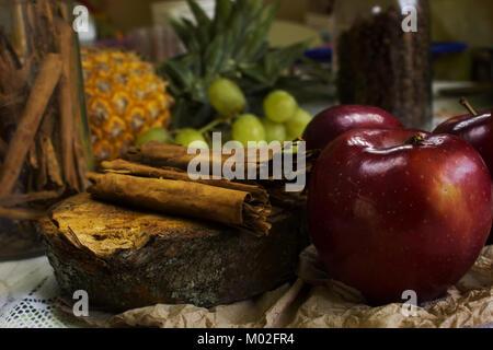 Scène confortable de grains de café sur bois rustique, des bâtons de cannelle, des pommes rouges, verts Banque D'Images