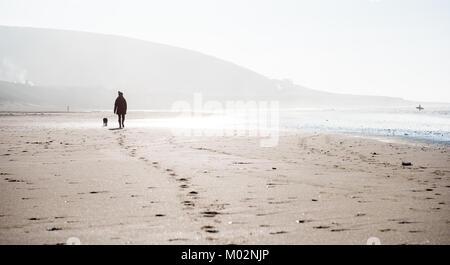 Balade sur la plage de Croyde avec chien en hiver Banque D'Images