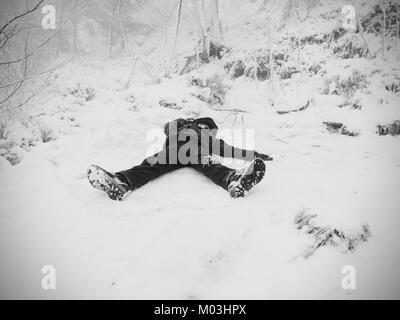 Funny boy laying in snowdrift. Kid jouer jeu en poudreuse fraîche sur Stony Hill. Tempête de neige et par temps Banque D'Images