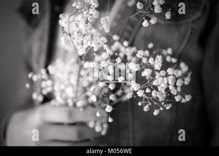Girl's hand holding blanc délicat gypsophile fleurs contre poitrine en noir et blanc Banque D'Images