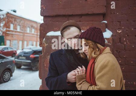 Young man and woman embracing près de brick coin de bâtiment. Rue d'hiver. La vie privée dans les endroits reculés Banque D'Images