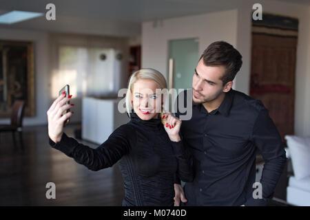 Happy young couple élégant costume noir en prenant l'intérieur selfies Banque D'Images