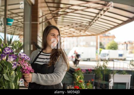 Small business concept. Femme Smilng la cueillette des fleurs fleuriste dans un magasin de fleur. Banque D'Images