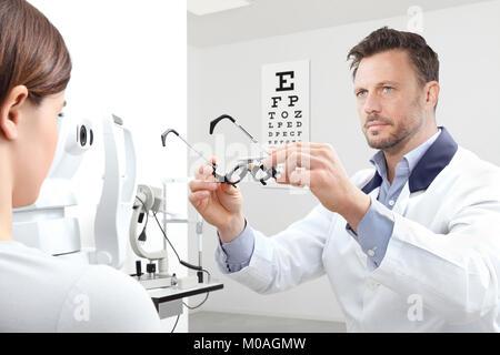 Optométriste avec châssis d'essai l'examen de la vue patient femme dans le bureau de l'opticien
