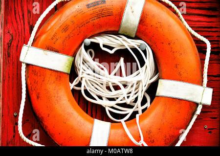 Libre de préserver la vie orange et blanc accroché sur la paroi rouge en bois Banque D'Images