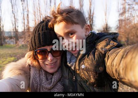 La mère et le fils prend un dans un parc public selfies en hiver. concept de personnes s'amusant Banque D'Images
