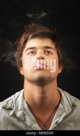 Jeune homme insouciant détendue fumeurs contre les mauvaises herbes
