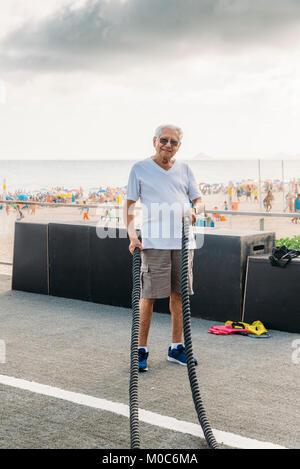 Parution: modèle homme plus âgé (80-89) l'exercice de combat avec corde au gymnase public à Ipanema, Rio de Janeiro, Banque D'Images