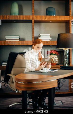 Businesswoman wearing glasses using digital tablet in office