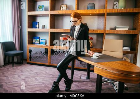 Attractive businesswoman travaillant sur une tablette numérique dans l'office.