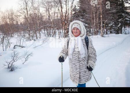 Sport d'hiver - la marche nordique. Senior woman randonnées en forêt froide. Ruddy heureux visage, en favorisant Banque D'Images