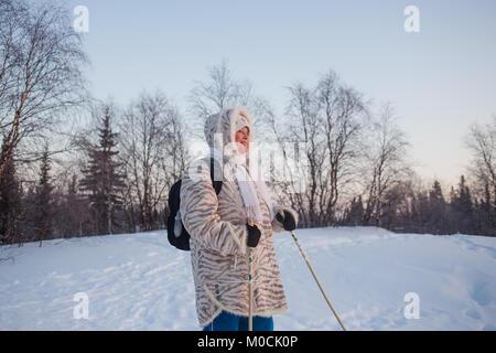 Happy senior man à coucher du soleil d'hiver en forêt. L'activité de marche nordique Banque D'Images