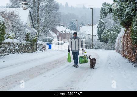 Killearn, Stirlingshire, Scotland, UK - 21 janvier 2018: Royaume-Uni - homme marchant avec chien jusqu'route enneigée Banque D'Images