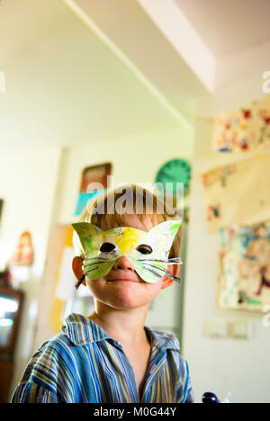 Un gros plan d'une année trois souriant dans son pyjama garçon portant un masque de chat à la main dans une cuisine Banque D'Images