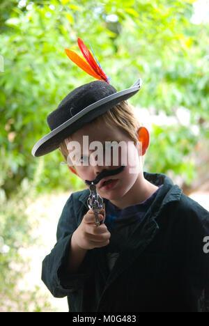 Portrait de cinq ans habillé comme un cowboy pointant son arme-jouet et à la caméra en staight avec arbres en arrière Banque D'Images