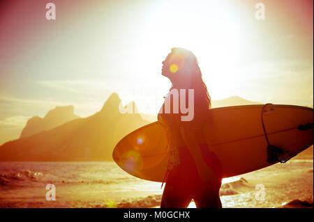 Méconnaissable silhouette de femme surfer autour de l'Arpoador, spot de surf populaire à Rio de Janeiro, Brésil Banque D'Images
