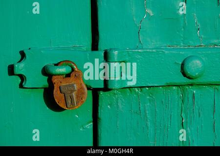 Ancien cadenas rouillé sur porte de garage peint en vert, Norfolk, Angleterre Banque D'Images