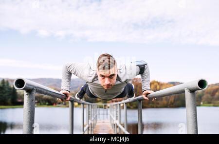Jeune homme avec le smartphone faire de l'exercice dans le parc. Banque D'Images