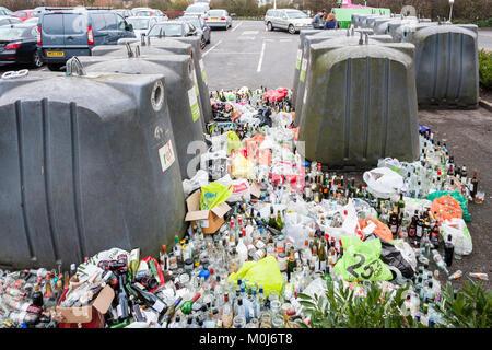 Verre plein et le débordement des bacs de recyclage dans le parc de voiture après Noël et Nouvel An Banque D'Images