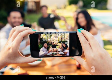 Les jeunes s'amusant à l'extérieur. Group of friends posing tandis que leur ami prendre une photo avec son téléphone Banque D'Images