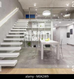 Loft avec mezzanine blanc escalier, table, chaises et ...