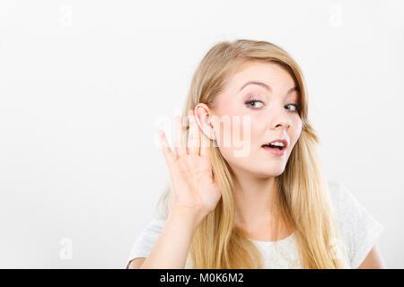 Gossip,rumeurs, murmure, concept d'audience. Jeune blonde Woman putting hand oreille d'entendre mieux. Studio shot sur fond blanc.