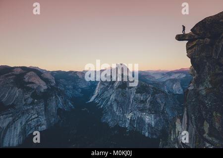 L'intrépide randonneur est debout sur un rocher en surplomb à l'égard célèbre Demi Dôme à Yosemite National Park Banque D'Images