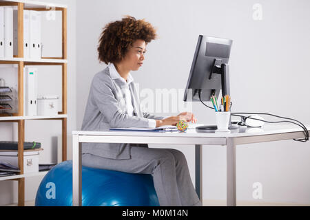Businesswoman Sitting on Fitness Ball working on Computer Banque D'Images