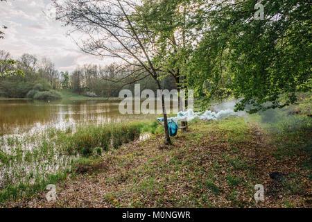 Jeune homme couché dans un hamac, holding de la fumée bleue torch Banque D'Images