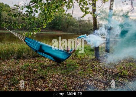 Jeune homme étendu dans un hamac avec torche de fumée bleue Banque D'Images